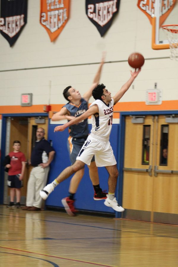 Eyes on the prize—Junior David Sabzehroo focuses on on making his lay-up, regardless of the tough defense on his back.