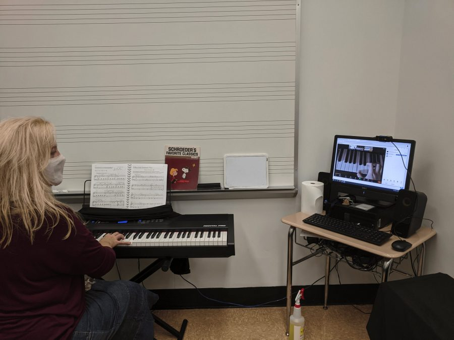 Hands seen through the screen—Dr. Janine Robinson teaches her piano class using a webcam in the piano lab. She is able to demonstrate piano techniques to her students while also viewing their hands on their keyboards.