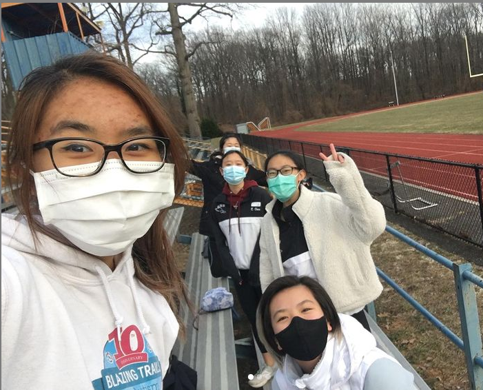 Meet you at the finish line—Members of the girls' track team gather together to take a picture at one of their meets. Despite the absence of fans and competitors in the bleachers and track, the girls keep pushing on in a COVID year.