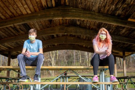 Teenage siblings wearing face masks sitting at a park grove outdoors keeping a social distance during the coronavirus pandemic.